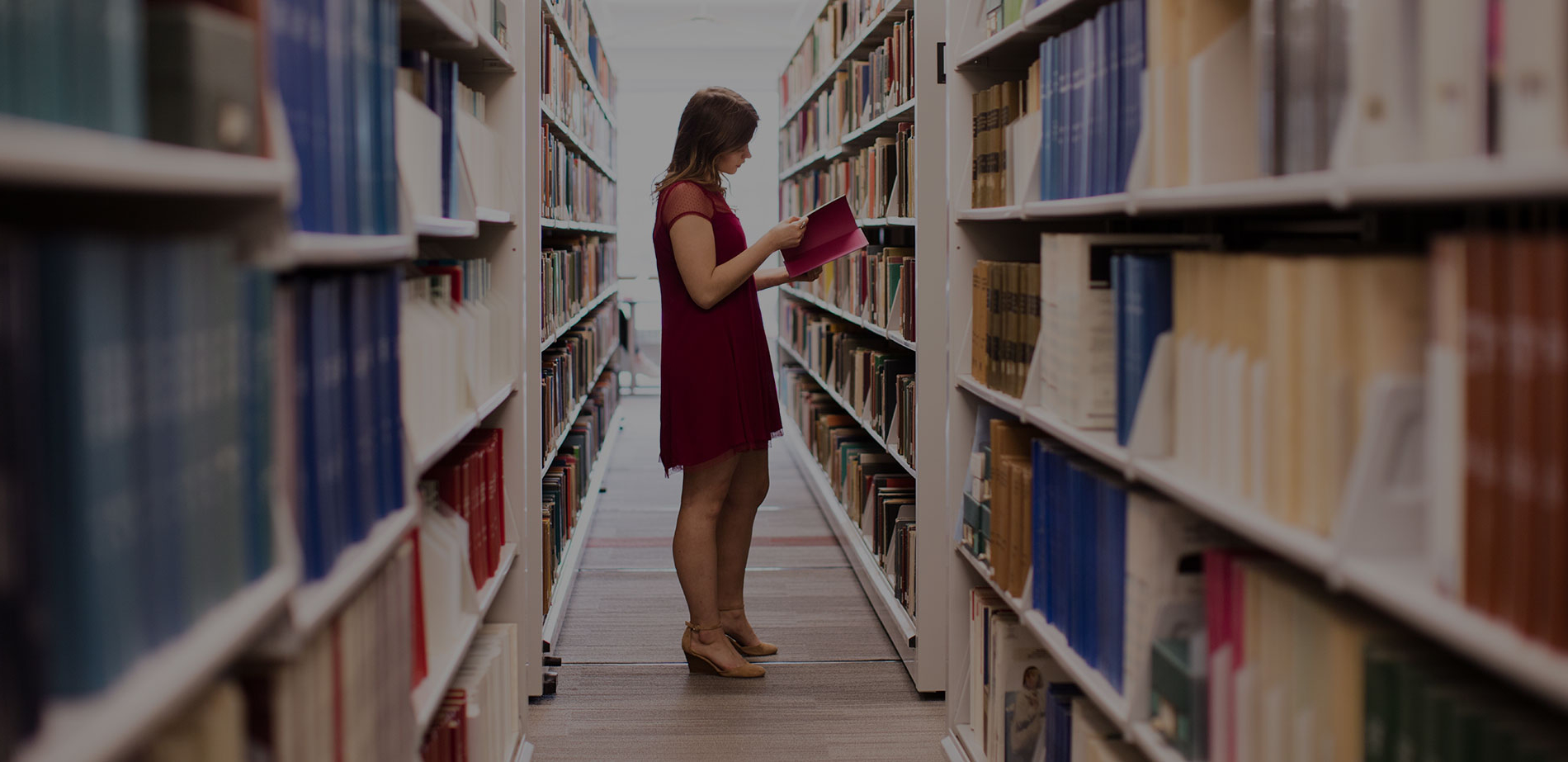 student looking at books in stacks